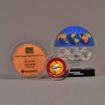 Grouping of three circular acrylic embedments awards with different items cast inside clear acrylic.