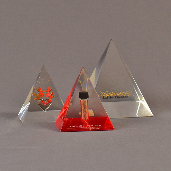 Grouping of three pyramid acrylic embedments awards - one with a dirt sample, one with brass images and one with text.