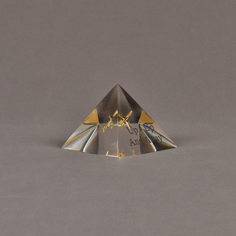 """Angle view of 3"""" x 3"""" pyramid acrylic embedment award with brass model of airplane cast inside."""