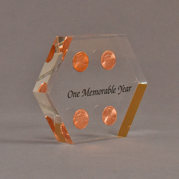"""Angle view of 4"""" x 5"""" hexagon acrylic embedment award with four pennies cast in clear acrylic and black text."""