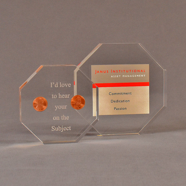 Two octagon acrylic embedment awards one with cast pennies the other with cast printed Janus Institutional Assets tagline.