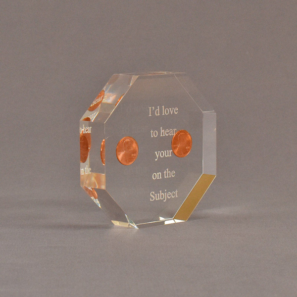 """Angle view of 4"""" x 4"""" octagon acrylic embedment award with two pennies cast in acrylic highlighted with laser engraving."""