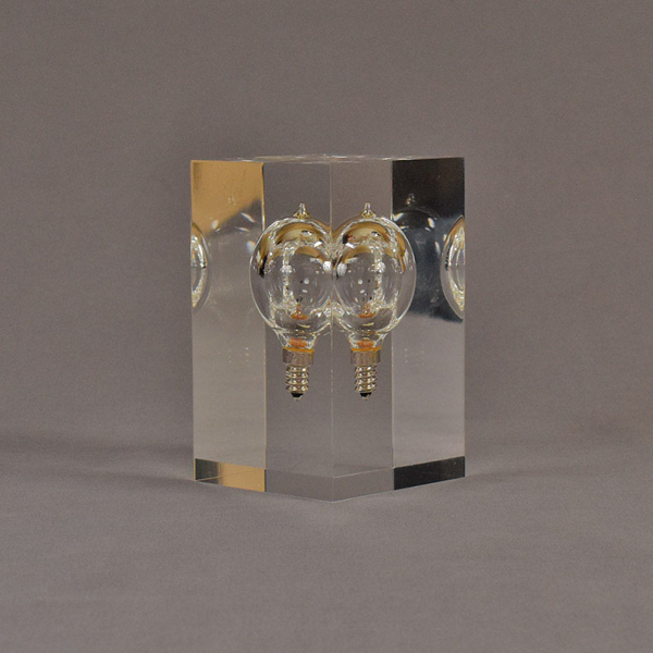 """Angle view of 3"""" x 3"""" x 5"""" rectangle block acrylic embedment award with lightbulb cast in clear acrylic."""