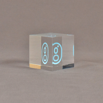 """Angle view of 2"""" cube acrylic embedment award with G logo printed on clear acetate and cast in acrylic."""