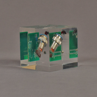 """Angle view of 3"""" cube acrylic embedment award with electronic component cast into crystal clear acrylic."""