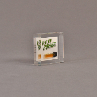 """Angle view of 3"""" square acrylic embedment award with Eco Power logo and vial of oil cast in acrylic."""