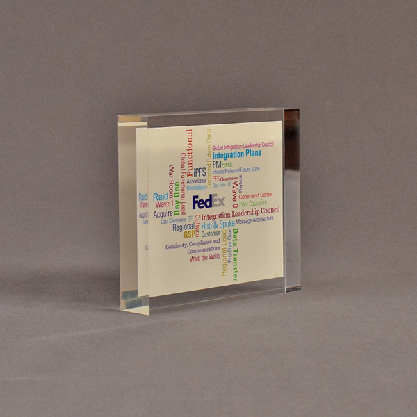 """Angle view of 4 1/2"""" square acrylic embedment award with FedEx logo and tag lines cast in clear acrylic."""