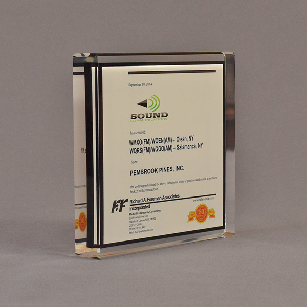 """Angle view of 6"""" square acrylic embedment award with Sound Comunications logo and text cast in acrylic."""