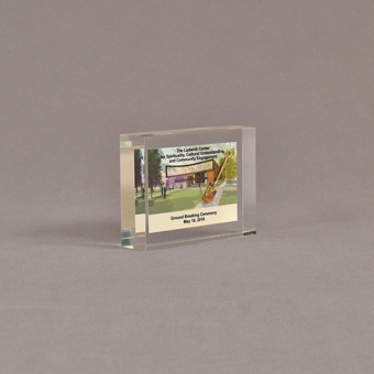 """Angle view of 3"""" x 4"""" rectangle acrylic embedment award with mini ground breaking shovel and building cast in acrylic."""