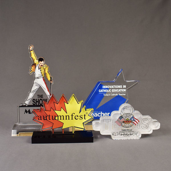 Four custom shaped Elite Series LaserCut™ Acrylic Awards showing a Market 58 trophy. Autumnfest trophy, Texas Roadhouse trophy and Catholic Teach trophy.